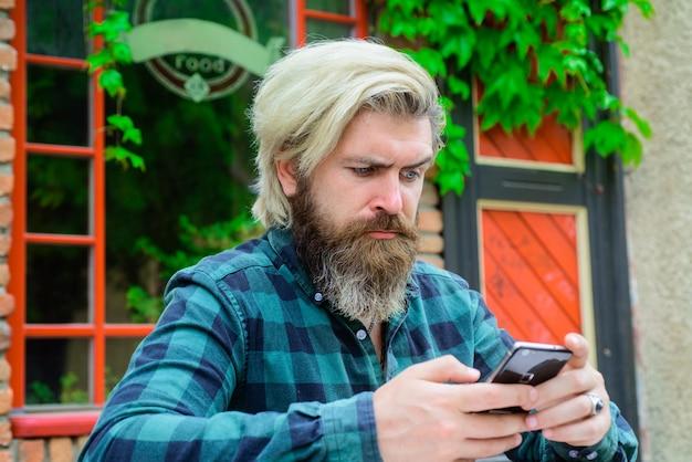Серьезный мужчина с телефоном на открытом воздухе работа в сети онлайн-игры выигрывает онлайн цифровая работа внештатный сотрудник