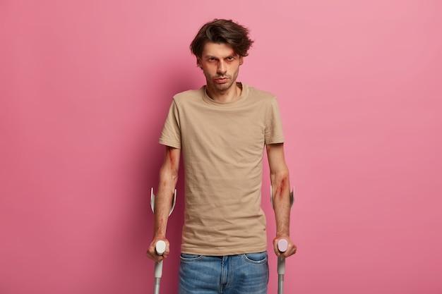 Uomo serio con le grucce, cerca di camminare e riprendersi dopo un caso accidentale, ascolta attentamente i consigli del medico, vestito con abiti casual, posa sul muro rosa. assistenza sanitaria e concetto di supporto medico
