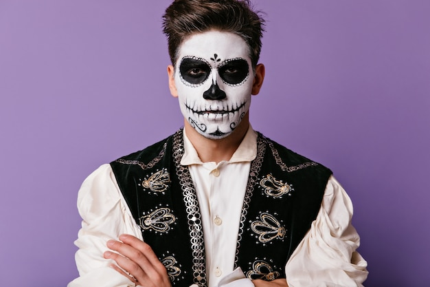 Serious man with skull-shaped mask poses on isolated wall. guy in black vest with embroidery