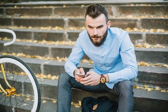 Serious man with smartphone sitting near bicycle