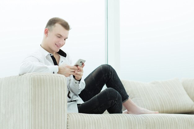 彼のリビングルームのソファに座っているスマートフォンを持つ深刻な男