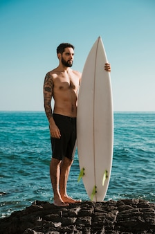 Serious man with surfboard standing on rock