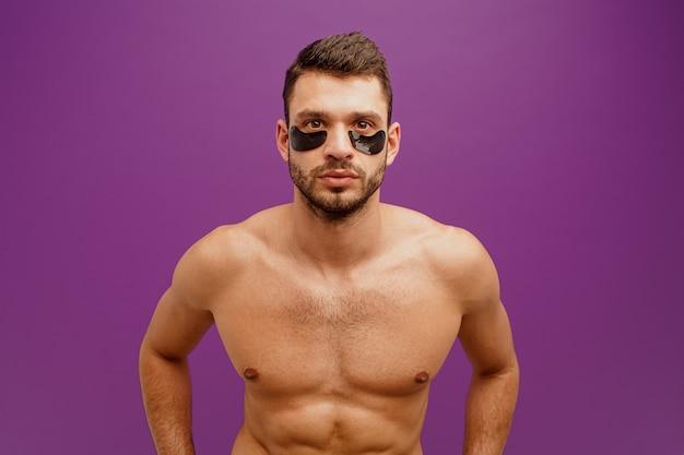 Серьезный человек с повязкой под глазами на лице. бородатый парень с идеальной кожей смотрит в камеру. концепция ухода за кожей лица. изолированные на фиолетовом фоне. студийная съемка. копировать пространство