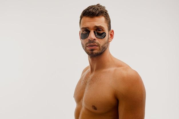 Серьезный человек с повязкой под глазами на лице. бородатый парень с идеальной кожей смотрит в камеру. концепция ухода за кожей лица. solated на белом фоне. студийная съемка. копировать пространство