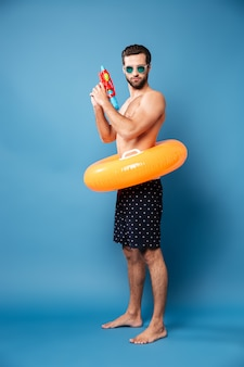 Serious man with water gun standing isolated
