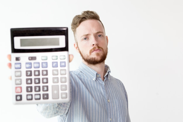 Serious manager stretching hand with calculator