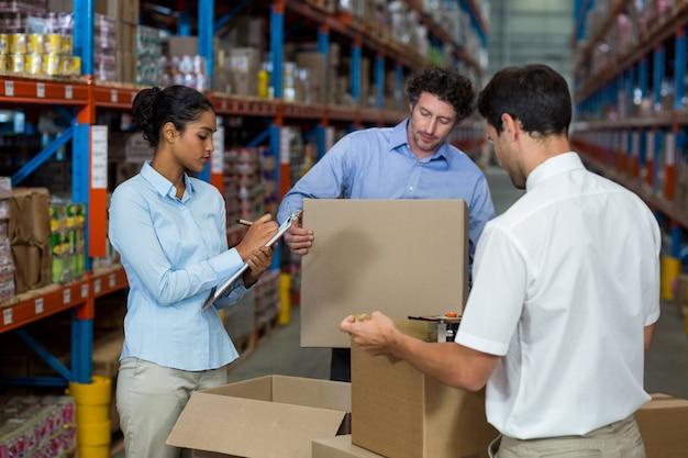 Серьезные менеджеры проверяют некоторые картонные коробки