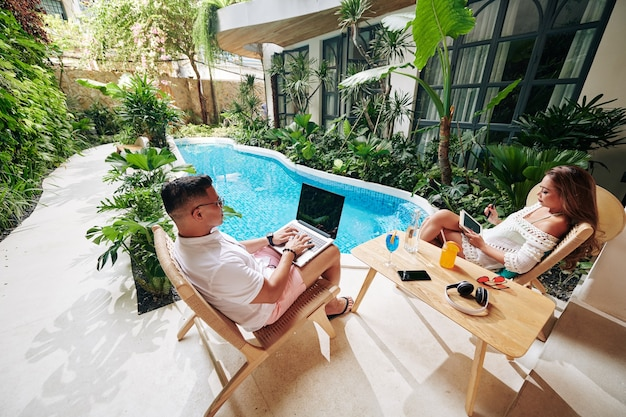 裏庭のプールの近くに座って、カクテルを飲み、ガジェットに取り組んでいる深刻な夫婦