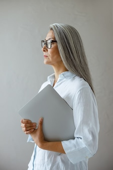 Serious mature asian businesswoman holds laptop standing near grey stone wall