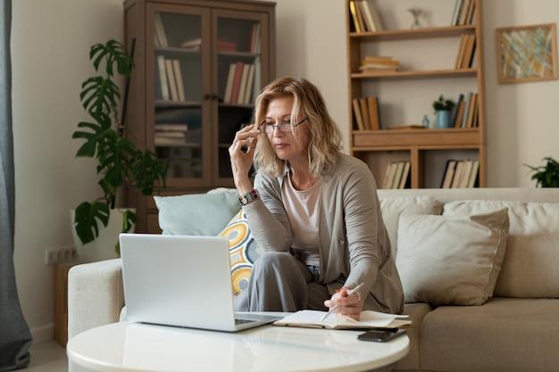 リビングルームでネットワークを構築しながらラップトップの前に小さなテーブルでソファに座っているカジュアルウェアの深刻な成熟した金髪の実業家