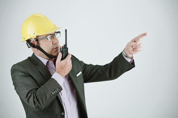 작업자에게 프로젝트 계획을 설명하면서 워키토키를 사용하여 작업 헬멧과 안경을 쓴 성숙한 건물 계약자 또는 엔지니어