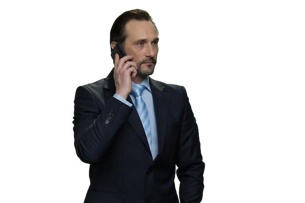 Серьезный зрелый бизнесмен звоня с мобильного телефона. изолированные на белой стене