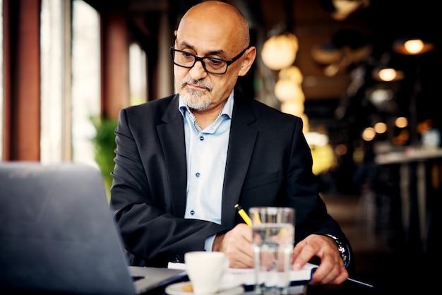 深刻な成熟したビジネスマンは、ラップトップを見て、コーヒーショップで彼のノートに書いています。