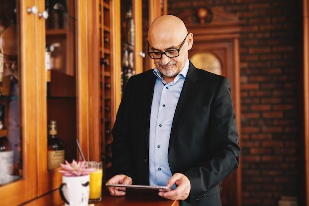 深刻な成熟したビジネスマンがコーヒーショップで楽しみながら彼のタブレットで探しています