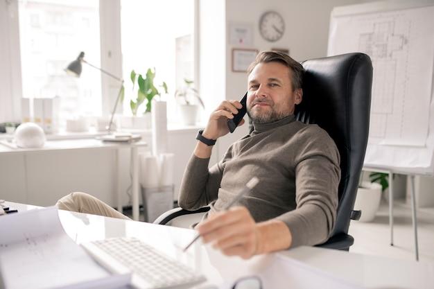 深刻な成熟したビジネスマンまたはオフィスのデスクでクライアントに相談しながら耳でスマートフォンを保持しているエージェント
