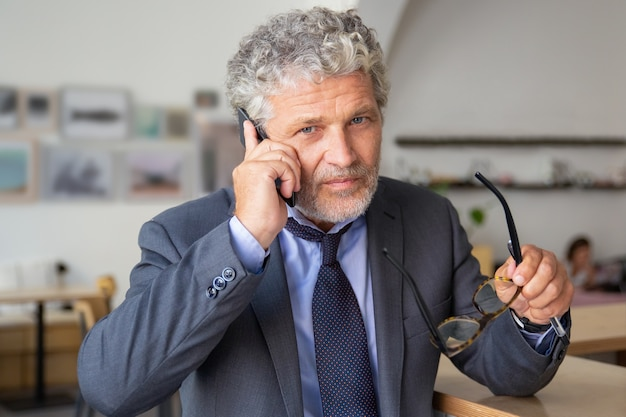 Серьезный зрелый бизнесмен разговаривает по мобильному телефону, стоя в коворкинге, опираясь на стол, глядя в камеру, держа очки