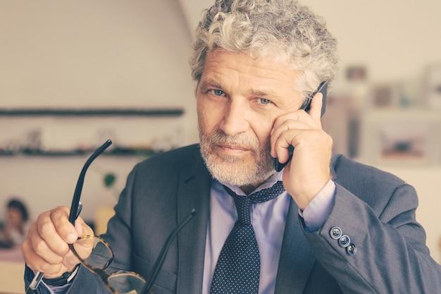 携帯電話で話し、コワーキングに立って、机に寄りかかって真面目な成熟したビジネスマン