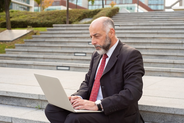 Serious mature businessman using laptop in street