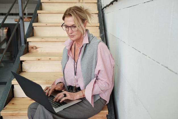 Serious mature businesswoman focused on work issues sitting on stairs and examining files on laptop