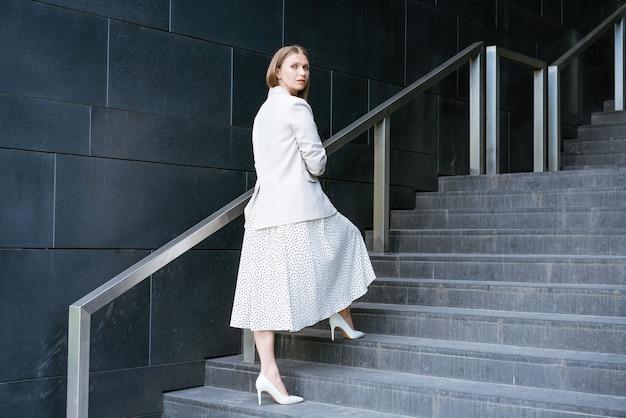 オフィスビルのcoacの前の階段に立っているエレガントなドレスを着た真面目な成熟した実業家...