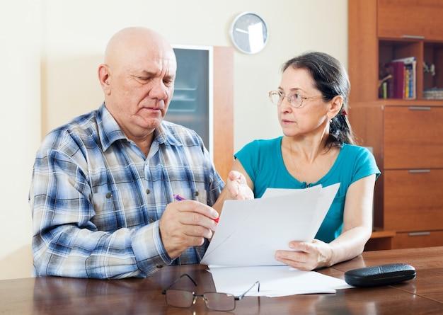 Серьезная пожилая супружеская пара заполняет анкету
