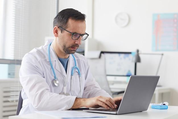Серьезный зрелый врач в очках сидит за столом и печатает на портативном компьютере в офисе