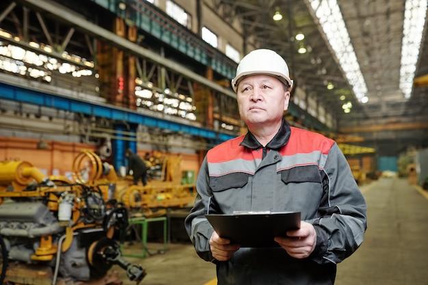 생산 공장에서 일하는 문서를 들고 헬멧을 쓴 진지한 성숙한 엔지니어