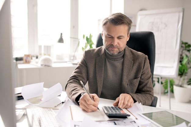 深刻な成熟したエンジニアまたは会計士とペンと電卓でオフィスの机に座っている間にノートにメモをとる