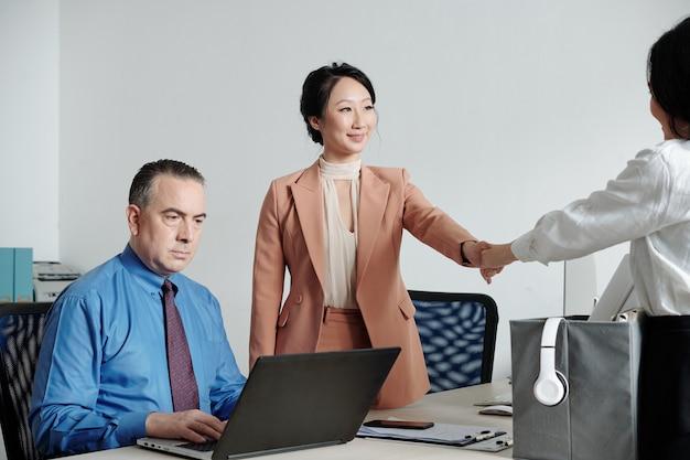 노트북 작업을 하는 진지한 성숙한 기업가, 그의 동료가 새 회사원과 인사하고 악수