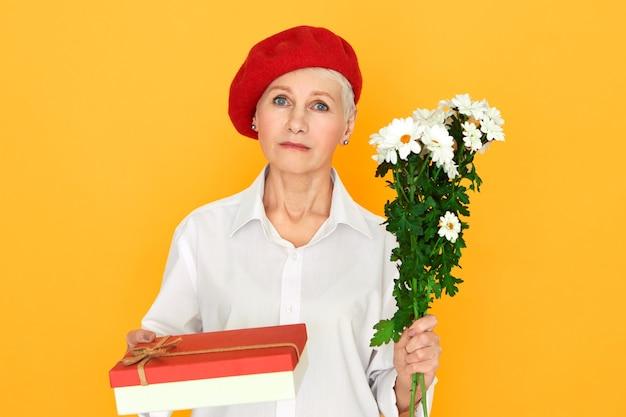 Grave donna europea matura con i capelli corti in posa isolato nel cofano rosso che tiene mazzo di margherite e scatola di dolci che fanno regalo di compleanno. elegante donna di mezza età che ti dà i fiori