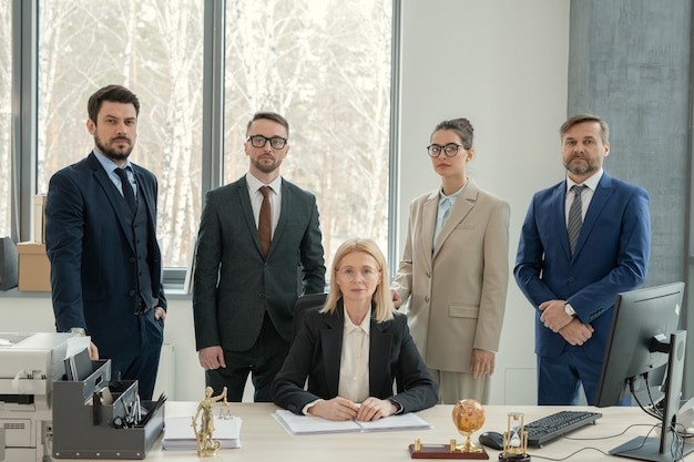 Serious mature female chef of law firm surrounded by lawyers sitting with documents at desk in modern office