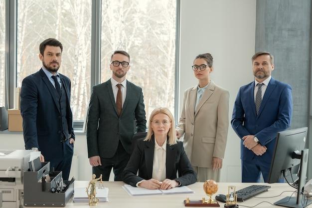 Серьезная зрелая женщина-шеф-повар юридической фирмы в окружении юристов, сидящих с документами за столом в современном офисе