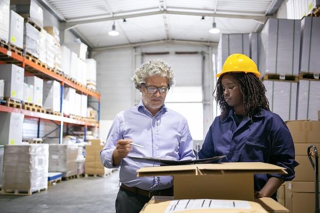 倉庫のチェックとフォームの記入中に黒人女性従業員に相談する真面目な成熟した検査官。コピースペース、正面図。労働と検査の概念