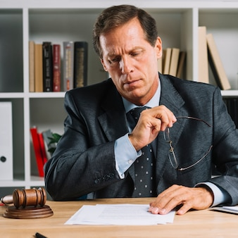 Serious mature lawyer reading document on desk in the courtroom