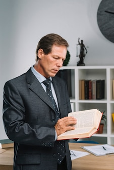 Серьезный зрелый адвокат, читающий книгу закона в зале суда