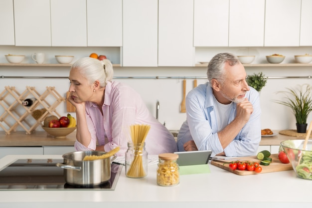 Serious mature loving couple looking at different sides at kitchen.