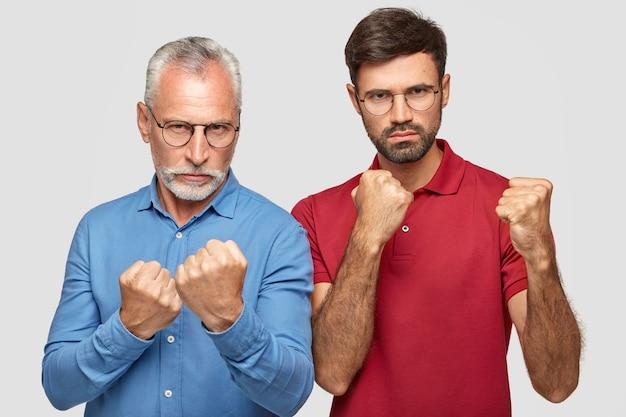 真面目な成熟した男と彼の大人の息子は、保護または防御のジェスチャーで拳を握りしめます