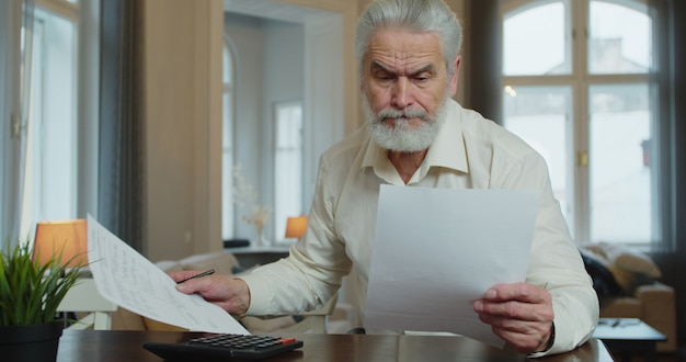 Serious mature man calculating bills, checking finances manage personal finances seated at table at home.