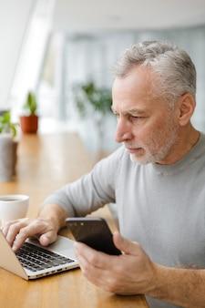 Серьезный зрелый мужчина пьет кофе во время работы с ноутбуком и мобильным телефоном в кафе в помещении