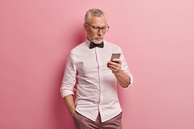 Serious mature man uses smartphone, reads news online, keeps hand in pocket, being always in touch, isolated over pink background.