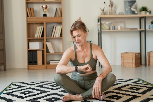 Серьезная зрелая спортсменка смотрит на умные часы, сидя на полу в гостиной и отдыхая после домашней тренировки