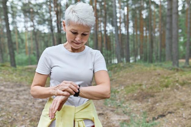 Grave atleta donna matura che imposta un fitness tracker per monitorare la frequenza cardiaca durante l'esecuzione nel parco