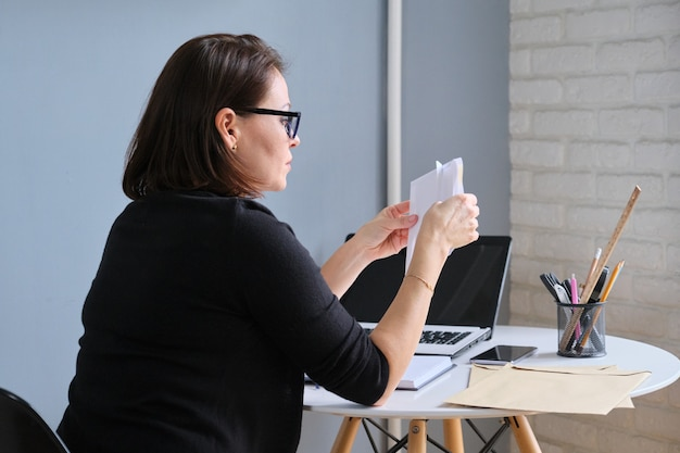 Serious mature woman holding business papers in hands documents