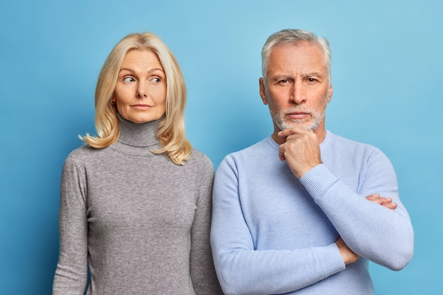Serious mature woman and man stand closely to each other have thoughtful expressions dressed in casual clothes isolated over blue wall