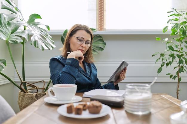 在宅勤務の真面目な熟女。朝のテーブルに座って、朝食をとり、デジタルタブレット、ビジネスノートブックを使用してパジャマを着た女性