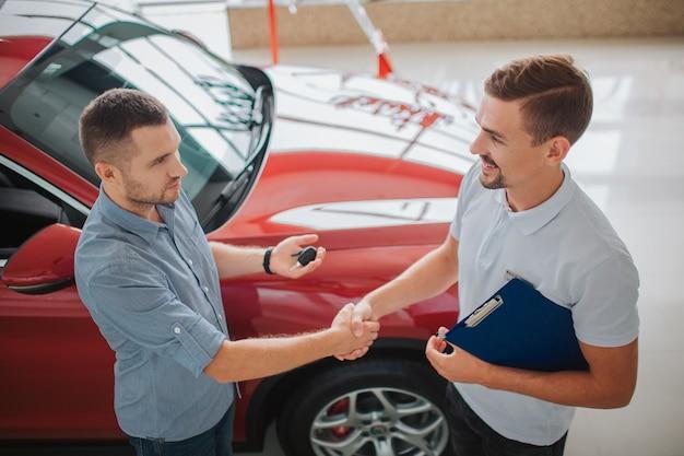 진지한 사람들이 서서 서로의 악수를합니다. 구매자는 자동차 열쇠를 가지고 있습니다. 딜러는 태블릿을 잡습니다. 그들은 거래를했다. 빨간 차는 왼쪽의 남자에 속합니다.