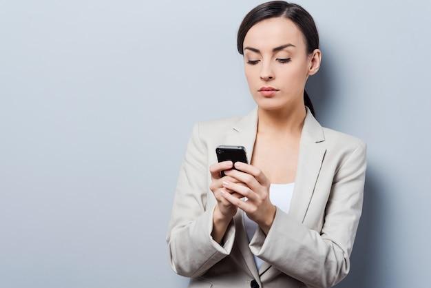 Серьезный разговор. красивая молодая деловая женщина держит мобильный телефон и смотрит на него, стоя на сером фоне