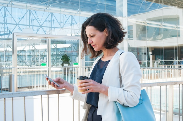 Serious mid adult businesswoman texting message at coffee break