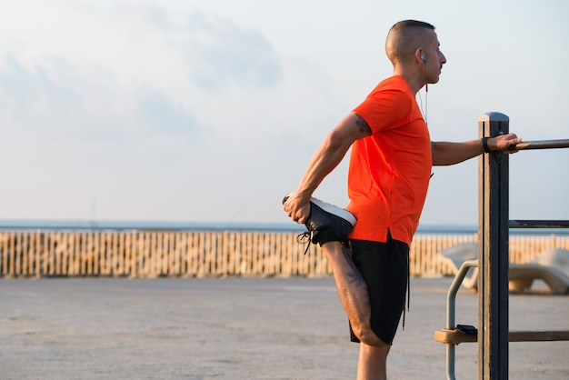 Serious mid adult male athlete stretching leg