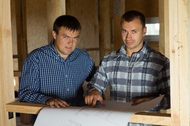 Serious middle age architect men at building site with blueprint looking at camera